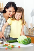 Adorable little girl cutting vegetables with her mother in the kitchen